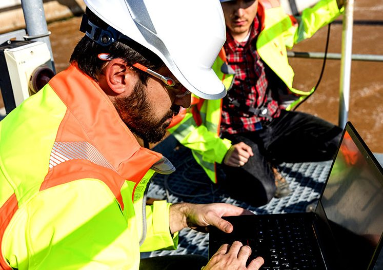 Field Engineer working on laptop in the field while wearing a hardhat