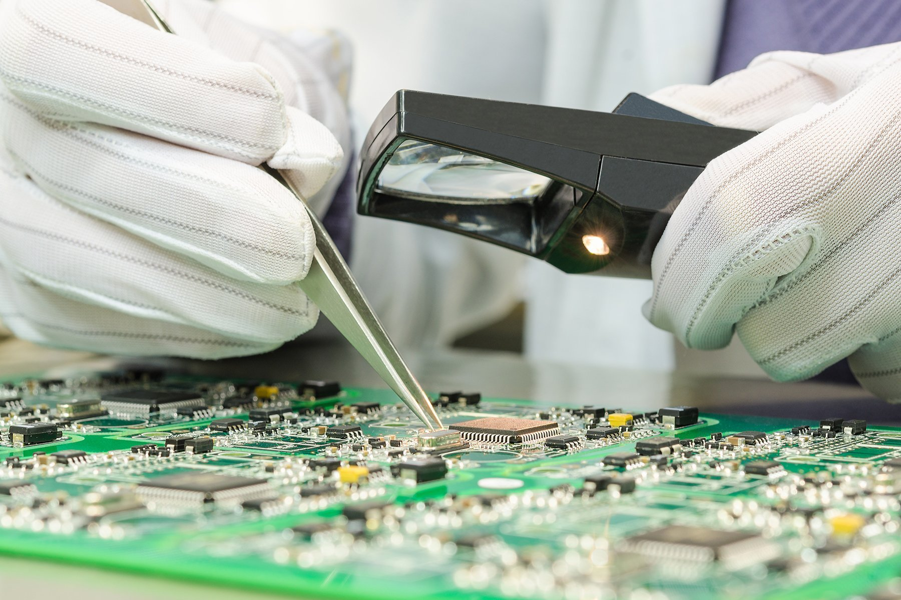 Person working on circuit board with tweezers and a magnifying glass