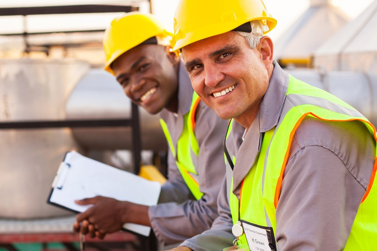 Two workers with hard-hats smiling